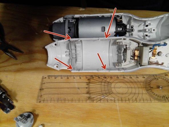 Wenn die Schrauben raus sind kann man  das Gehäuse vorsichtig aufhebeln. Dafür muss an den 4 markierten Stellen mit einem schmalen Schraubenzieher oder Kunststoffhebel angesetzt werden. Die Stellen befinden sich bei 5 und 10 cm von links gemessen.