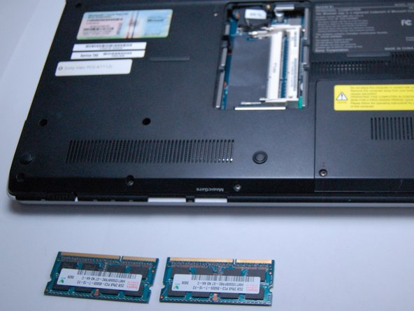 Image 3/3: Lift and slide out the RAM to remove it from the slot.