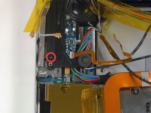 Image 1/1: Remove the single black T6 Torx screw securing the left speaker.