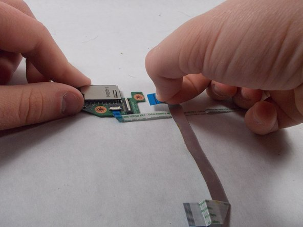 Repeat the previous step and this step with the other ribbon cable that is attached to the SD Card Reader/USB Port.