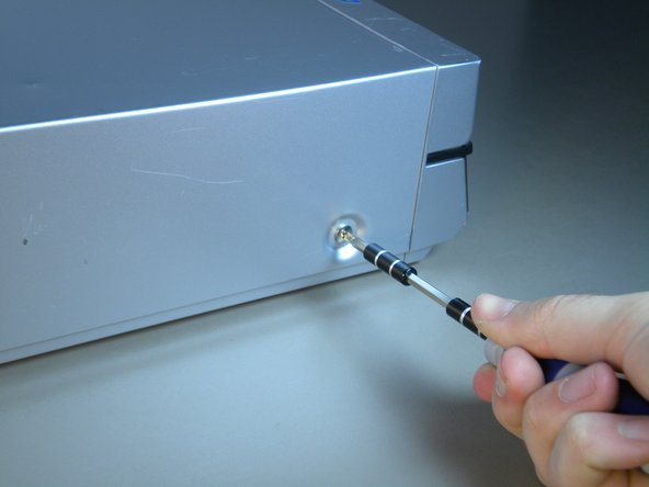 Image 2/3: Remove the screw that is on the right side of the panel facing you.