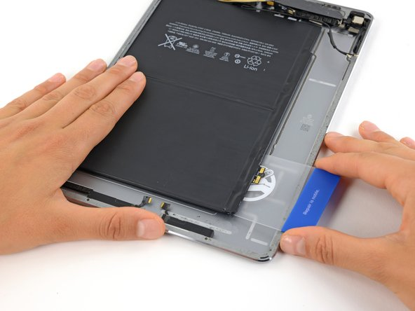 Image 2/2: Insert a plastic card underneath the battery contacts.