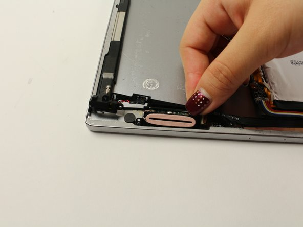 Lift the headphone jack, coiled wire, and cable, peeling the adhesive back.