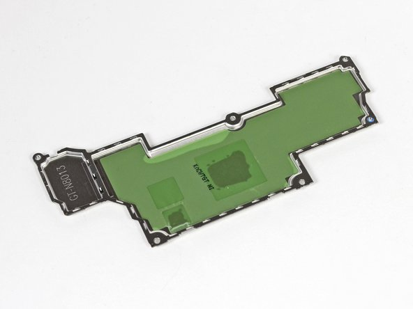 Image 2/2: The green film on the insides of the EMI shields holds thermal paste and thermal pads in place, which help move heat away from the motherboard through small holes in the tops of the shields.