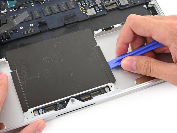 Use a plastic opening tool to slowly and carefully peel the trackpad cover plate up off the upper case.