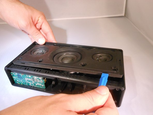 Using the plastic opening tool, flip open the speaker panel.