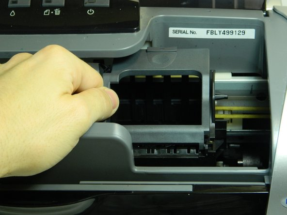 Gently slide the ink cartridge carrier by hand to the left to gain access to the inside of the left panel.