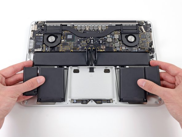 Image 1/3: Before installing a new battery, remove all the old adhesive from the MacBook Pro's case.