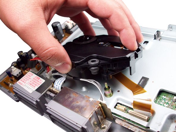 Lift the optical drive off of the PlayStation.