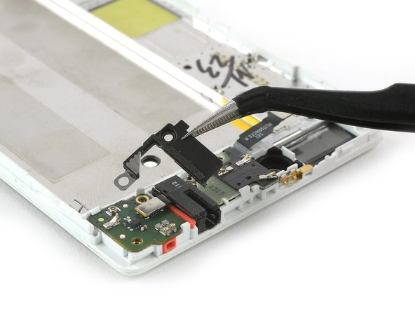 Use a tweezer to remove the plastic bracket which is covering the corner of the headphone jack.