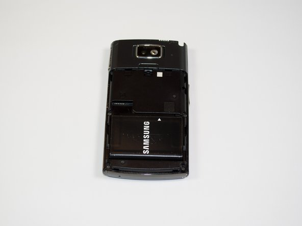 Image 1/1: While button is depressed, remove the back panel of the phone by sliding off (not shown in picture).
