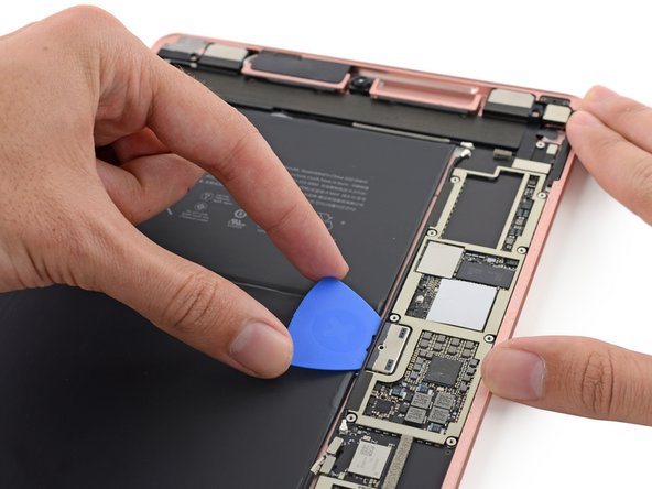Image 2/3: Our fingers are itching for chips, but for now we restrain ourselves and settle for isolating the battery. One precisely-placed [https://www.ifixit.com/Store/Parts/Battery-Isolation-Pick/IF145-304-1|pick|new_window=true] separates the battery contacts from the logic board.