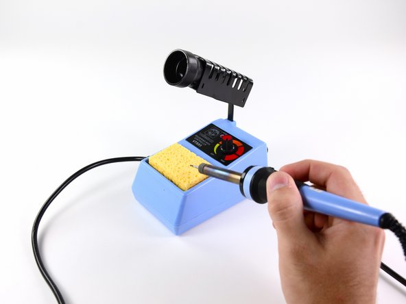 """Image 2/3: Melt another small ball of solder onto the tip of the soldering iron, but do not wipe it off. This is called """"tinning"""" the iron, and will improve heat conductivity, allowing you to solder more quickly and efficiently."""