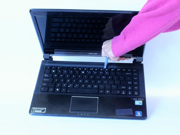 Insert a plastic opening tool or a flat-head screwdriver between the laptop body and the keyboard.
