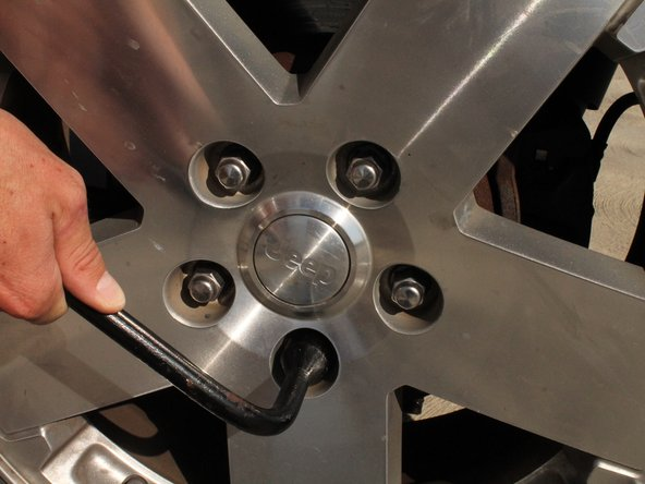 To physically loosen the lug nuts, use the lug wrench and push down very hard in a counter-clockwise direction.