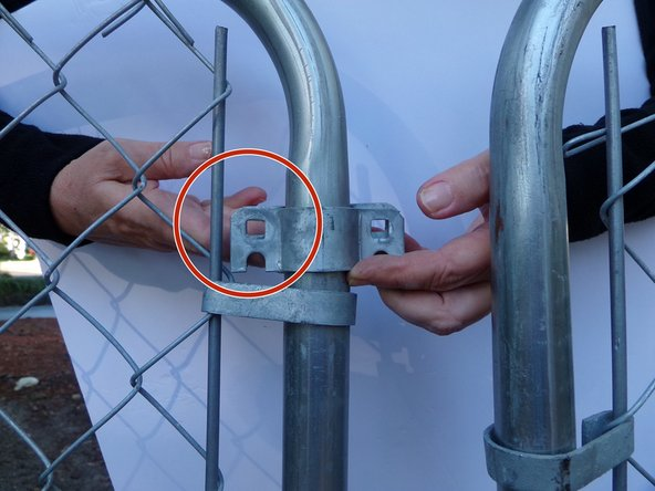"Using a a 1/2"" socket wrench or adjustable wrench, bolt the two latch plates on the inside of the gate frame together on  one end."