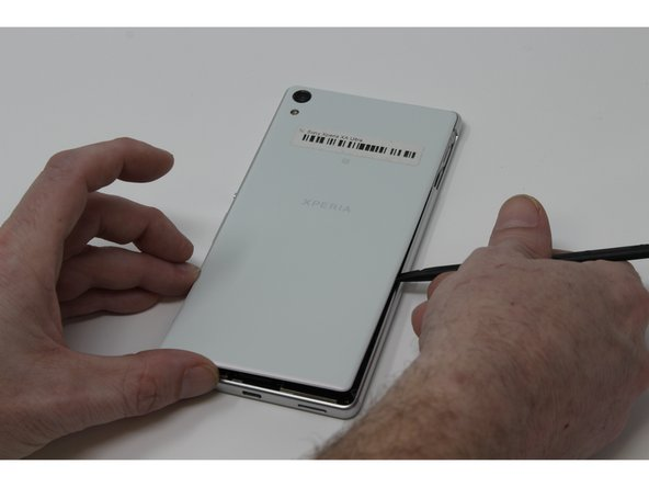 Carefully remove the back panel of the phone with a plastic spudger, or other flat and thin wedge tool. Work your way around the perimeter of the case, loosening and prying gently, until there is sufficient distance between the panel and phone.