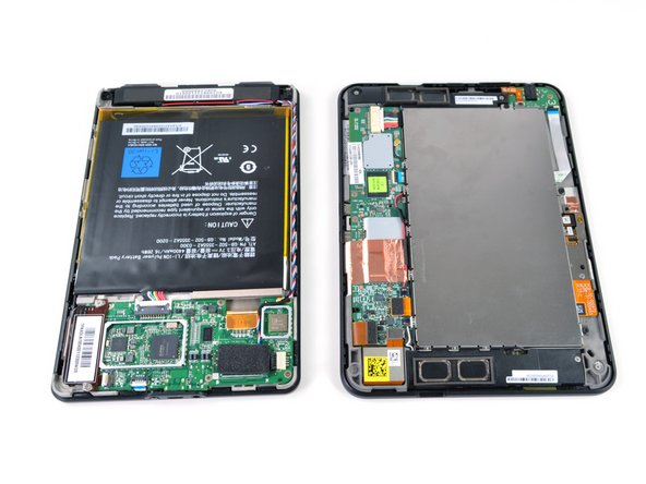 The newly revised Kindle Fire (left) and the Kindle Fire HD (right) lay side-by-side, both opened up and exposed to the sterile white lights of the iFixit teardown table.