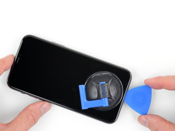 Re-insert your pick at the bottom edge of the iPhone, and slide it up the right side to continue separating the adhesive.