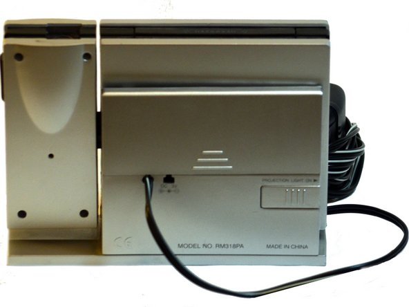 To access the A/C Power Adapter connection, remove the battery cover, located on the back of the clock.