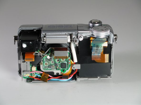Image 1/1: While the mother board is removed it is possible to get further into the camera itself to make more repairs.