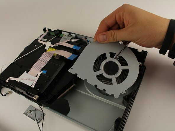 Remove the fan system by grabbing the edge of the top metal plate and lifting up with your hands.