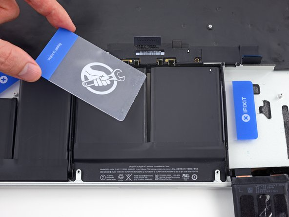 Remove the first plastic card that you inserted under the center-right battery cell.