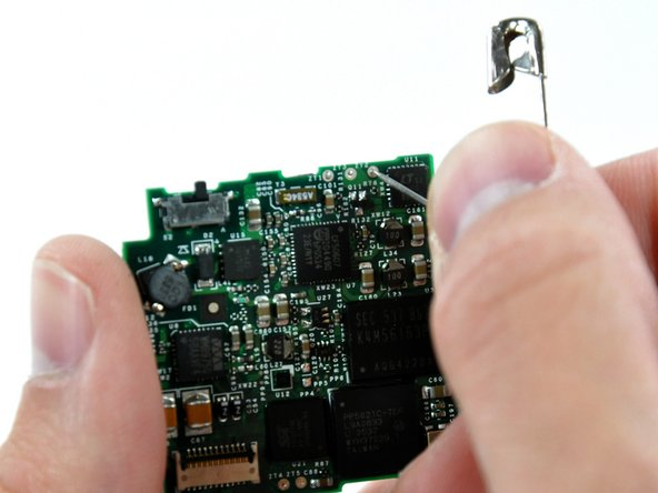 Image 1/2: To open the solder holes, open a safety pin and push it against the solder blocking the hole. At the same time, heat the same solder pad from the other side of the logic board. Opening the holes completely will require repeating this procedure several times from alternating sides of the logic board.