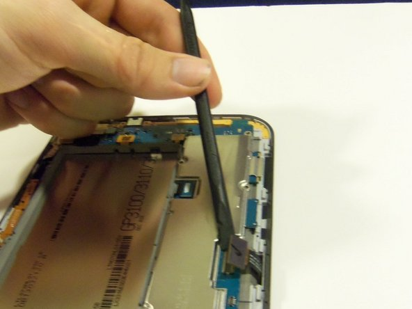 Using the plastic pry tool, release the touch screen flex cable from its socket.