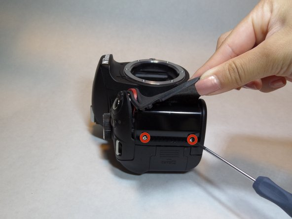 Lift the rubber grip using a plastic opening tool to locate and remove the two screws underneath using a Phillips screwdriver #00.