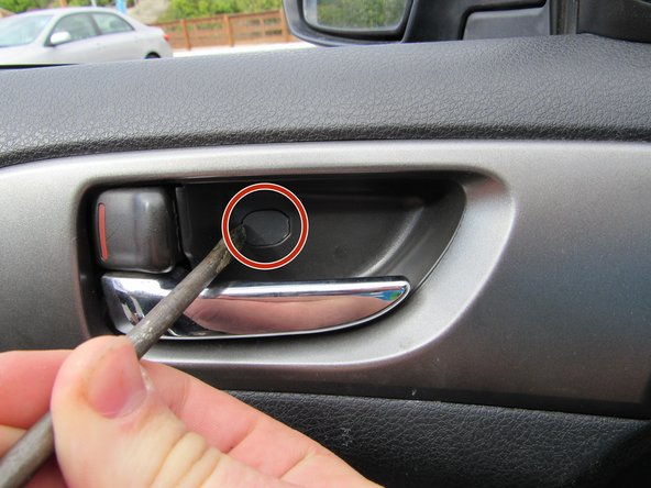 Pry up the plastic tab from inside the door handle housing.