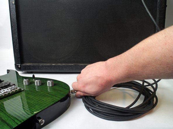 Plug an instrument into an amplifier using the newly repaired cable.