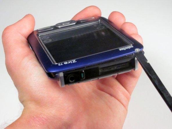 Faites tourner le téléphone pour que la prise casque soit face à vous. Exécutez l'extrémité plate du spudger sur tout le bord de l'appareil pour soulever délicatement l'affaire.