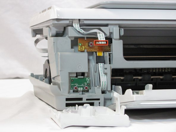 Image 1/2: Remove the cable connecting the top panel of the printer to the power button assembly.