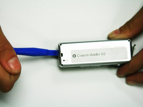 Use the plastic opening tool from the iFixit toolkit to separate the back from the front of the device. This can be done by wedging the opening tool into the space where the two sides of the cover on the device meet.