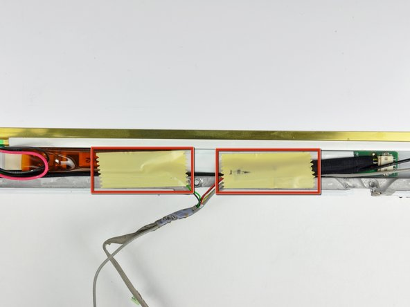 Remove the two pieces of tape covering the inverter/AirPort cables along the lower edge of the display.