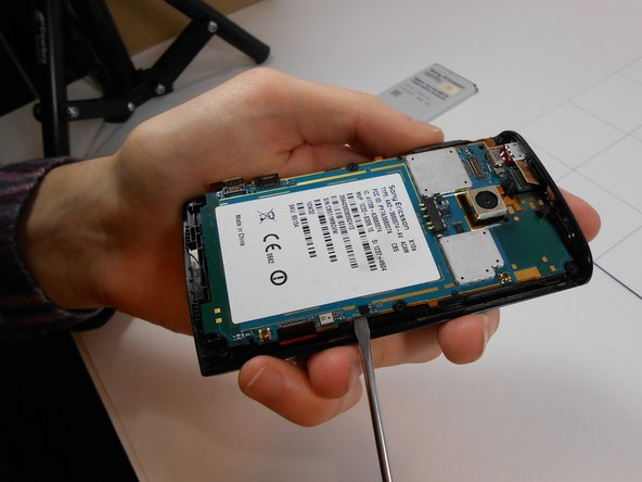 Gently insert a flat head screw driver under the logic board and pry to remove it from the phone casing. There should be a notch where a screw driver can fit as indicated in the image.