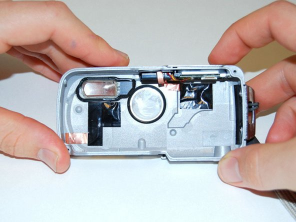 Lay front casing flat on surface as if you are looking through the camera lens.