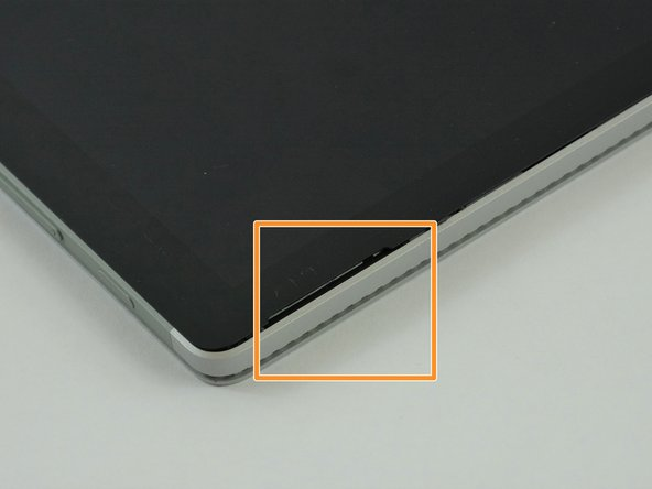 Place the Surface Book on a table with the camera towards you.  Place the metal spudgers in the indentations located on the top of the screen.