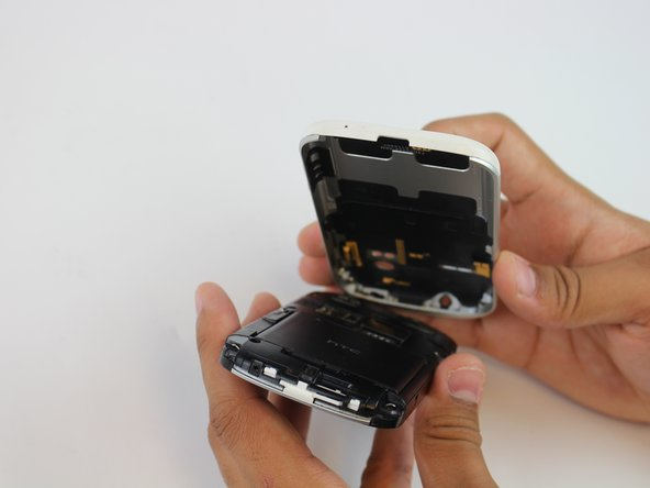 Gently press the Release Button located at the bottom of the phone in order to remove the back panel of the device.