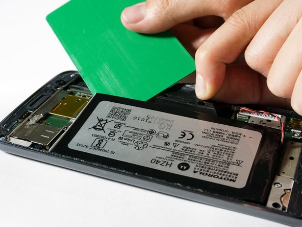 Lift  the black tape and slide a card under the battery.