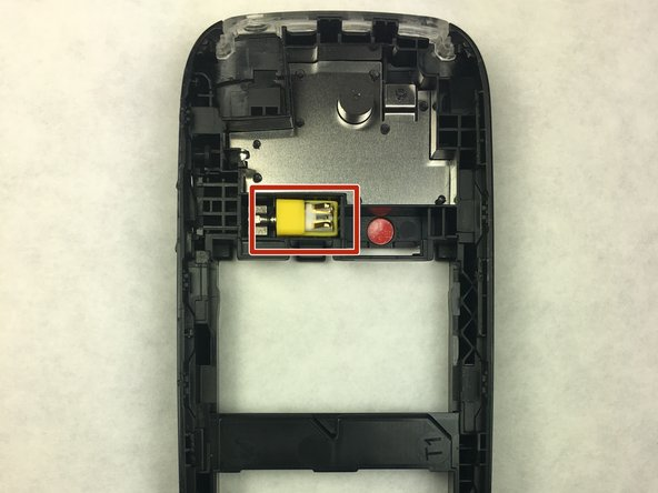 After separating the two plastic halves of the phone, take the plastic that does not have the motherboard attached to it. The plastic has a small yellow component with a lob-sided magnet within it. This is the vibrator of the phone, pull this piece out with your hand. This piece is free floating and will simply drop out.