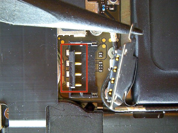 Image 3/3: Take notice of the position of the small black ground clip on the upper screw of the battery connector. This clip is attached only by the upper screw. When reinstalling, it must be aligned so the gold contact point will press against the back cover.
