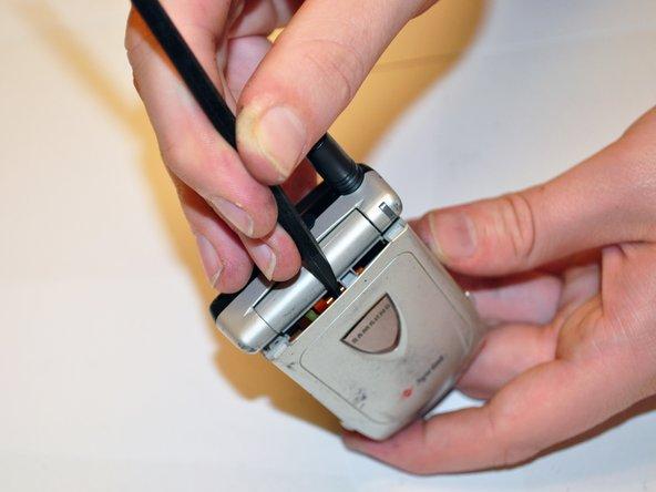 Une fois les deux vis retirées, utilisez le spudger pour retirer le couvercle avant du téléphone.