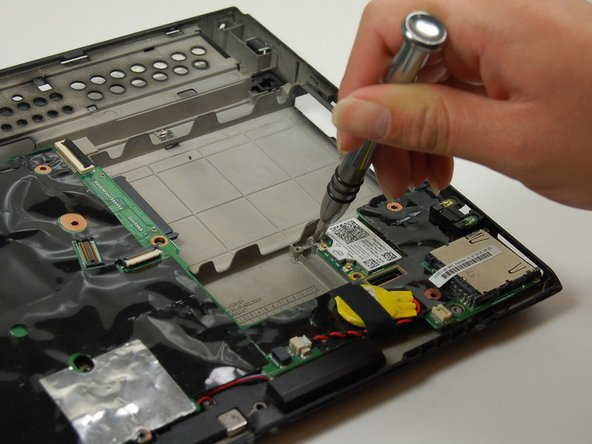 Remove a total of twenty-three 4.1mm screws from around the black plastic in the board.