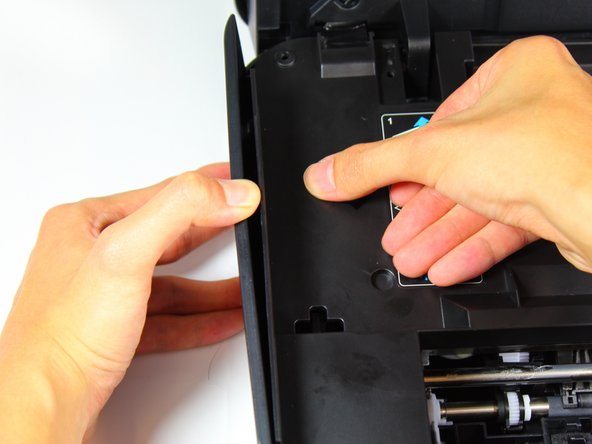 Detach the left-side panel by applying downward pressure on the internal protective cover with one hand and pulling the left-side cover with the other.