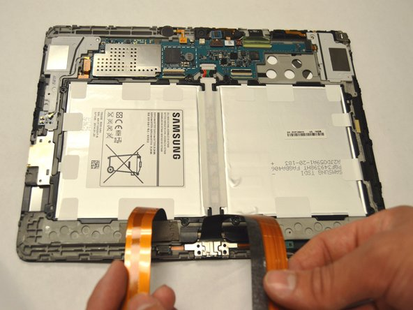 Remove the two ribbon cables that lie across the width of the battery and are connected to the motherboard. Place your finger underneath the ribbon cable and gently lift the cable upwards and off.