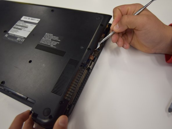 Next, move around the edges of the computer with the metal spudger prying off the casing. You should hear clicks as you do this; this is not the casing breaking, it is just popping off.