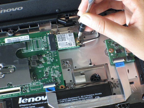 Use a screwdriver to remove the  single 3mm Phillips screw that is holding the WiFi card in place.