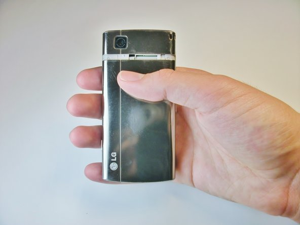 Place your thumb under the camera, apply a little pressure, and slide the cover toward the bottom of the phone.